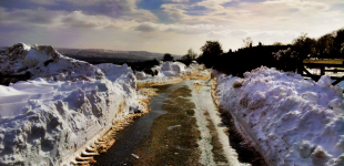 A clear road is flanked by high walls of snow.
