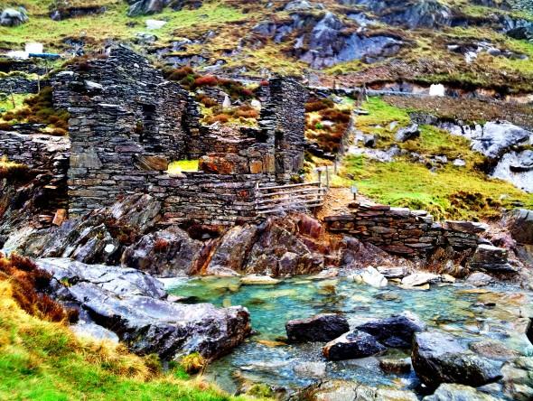 A ruined slate house by a blue pool